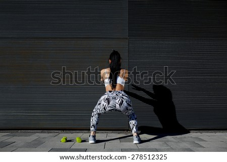 Back view athletic woman with perfect figure and buttocks doing squats against wall with copy space for your text message,fit female in sportswear squatting after training on black background outdoors - stock photo