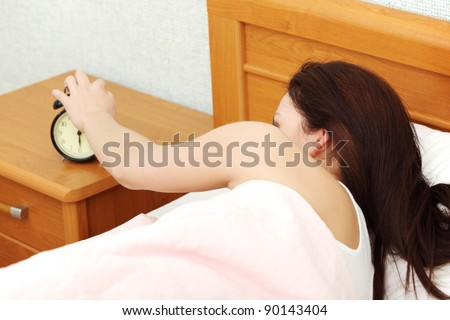 Back view closeup of a young beautiful woman reaching out her hand to turn off a black alarm clock.