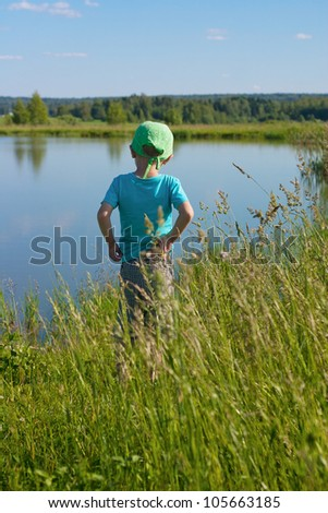 Back view cute 5 years old boy looking at the small lake - stock photo
