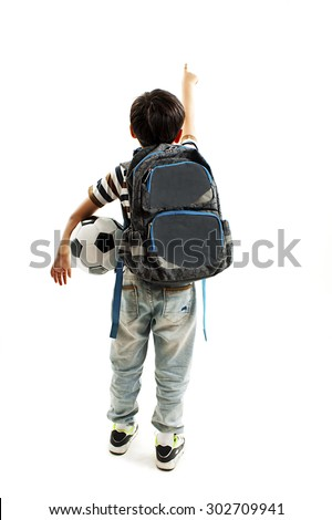 Back view Full length of young school boy holding a football, pointing at blank copy space. Isolated on white background - stock photo