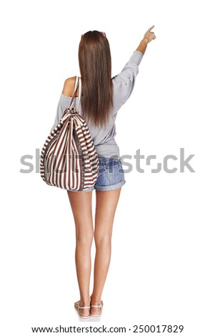Back view Full length of young slim tanned female in denim shorts with backpack pointing at blank copy space, isolated on white background - stock photo