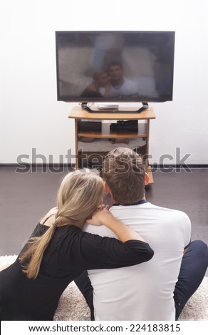 Back view girl friend  sits and rests on a strong sholder boyfriend  on the floor on TV background on white wall - couple embracing with each other Woman based near Man black and white casual dressed  - stock photo