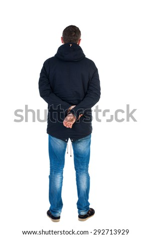 Back view handsome man in winter jacket  looking up.   Standing young guy in parka. Rear view people collection. backside view person.  . Man in warm jacket put his hands behind his back and standing - stock photo