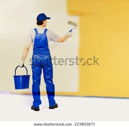 Back view house painter is painting yellow texture wall, view from behind Young full length man in blue overalls with painting tools Empty copy space for inscription  - stock photo