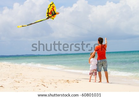 Back view if happy dad and son flying kite together
