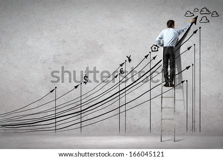Back view image of businessman drawing graphics on wall - stock photo