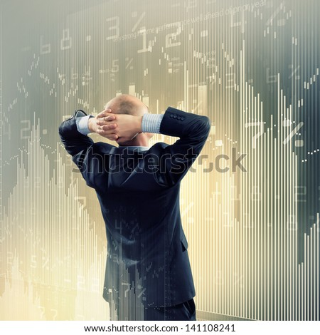 Back view image of businessman with arms crossed behind head - stock photo