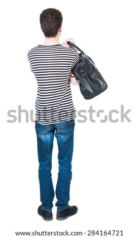 Back view man in jeans with bag. Standing young guy. Rear view people collection.  backside view person. guy in striped shirt with hands on hips standing. guy is throwing his bag on his right shoulder - stock photo