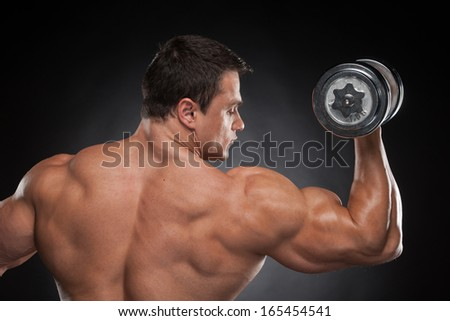 Back view muscular man lifting dumbbell up. Training isolated over black background