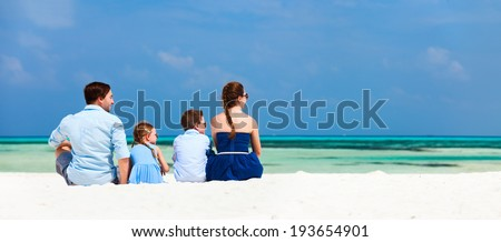 Back view of a beautiful family on a beach during summer vacation. Panorama perfect for banners