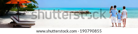Back view of a beautiful family on a beach during summer vacation. Wide panorama, perfect for banners - stock photo