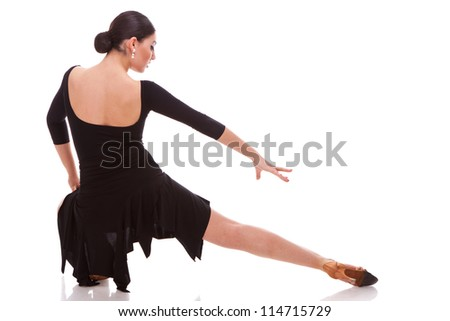 back view of a beautiful salsa dancer posing in a lunge dance move - stock photo