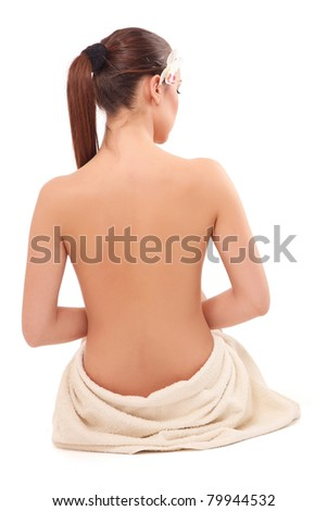 Back-view of a beautiful woman sitting on the floor, isolated on white