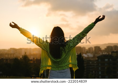 Back view of a blissful woman celebrating sport and fitness lifestyle success. Female athlete raising arms to the sky after exercising for relax towards beautiful sunset or morning over city skyline. - stock photo