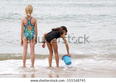 Back view of a blond and a brunette girl playing at a beach in Brazil.