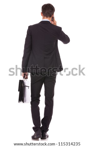 back view of a business man holding a briefcase and talking on his smartphone on white background - stock photo