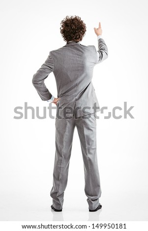 Back view of a businessman pointing at something. - stock photo
