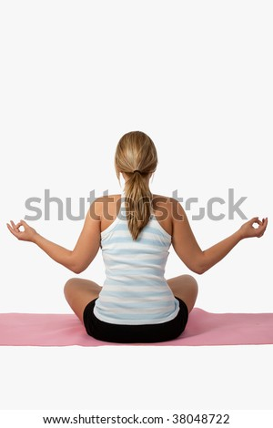 Back view of a caucasian blond woman wearing exercise clothes sitting on pink mat in lotus position meditating over white