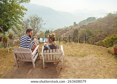 back view of a caucasian couple sitting and having breakfast with a mountain view in Nagarkot, Nepal - stock photo