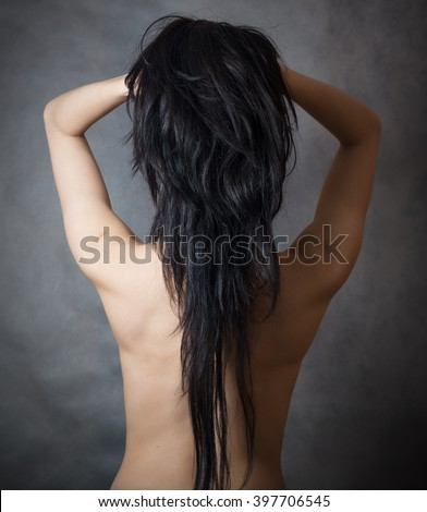 Back view of a caucasian woman with beautiful black hair on dark background. - stock photo