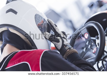 back view of a concentrated karting pilot sitting on his go-kart before starting a race in an outdoor go karting circuit - focus on the thumb - stock photo