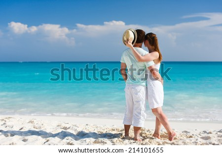 Back view of a couple on a tropical beach in Caribbean - stock photo