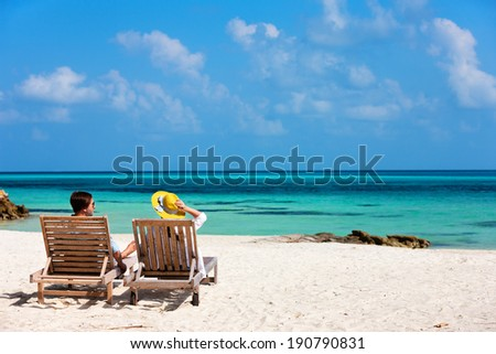 Back view of a couple relaxing on beach loungers during tropical vacation