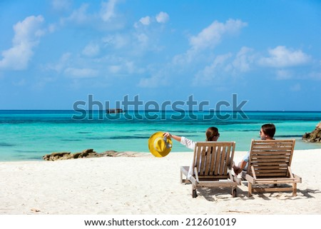 Back view of a couple relaxing on beach loungers during tropical vacation  - stock photo