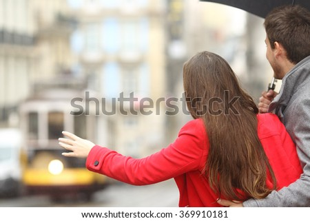 Back view of a couple waiting for public transportation and asking for a tram in the street in a rainy day - stock photo