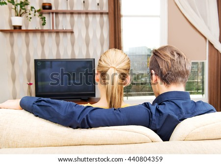 Back view of a couple watching tv at home