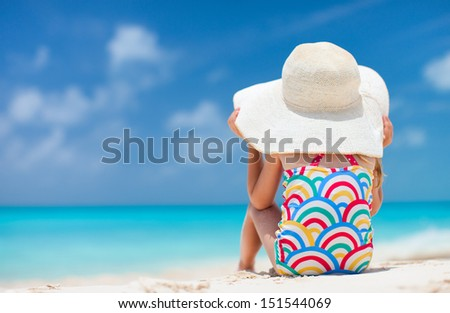 Back view of a cute little girl in a big straw hat at tropical beach  - stock photo