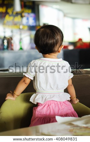 Back view of a cute young Indian girl/  baby/ kid/ babies/ one year old wearing pink skirt, Kerala, India. toddler standing holding green chair. looking at the lights, displays shopping center / mall  - stock photo