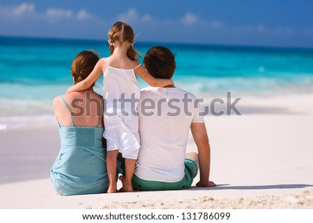 Back view of a family on a tropical beach - stock photo