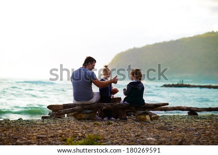 Back view of a father and his kids walking on the sea shore