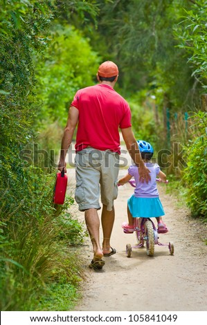 Back view of a father pushing his daughter on a bicycle on a summer day - stock photo