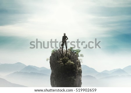 Back view of a female entrepreneur standing on the mountain peak while holding a briefcase