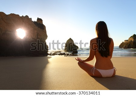 Back view of a full body of a girl wearing bikini doing yoga exercises in the beach at sunrise in front of the sun - stock photo