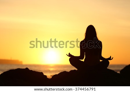 Back view of a full body of woman silhouette sitting doing yoga lotus pose exercises at sunrise with the sun horizon and ocean in the background - stock photo