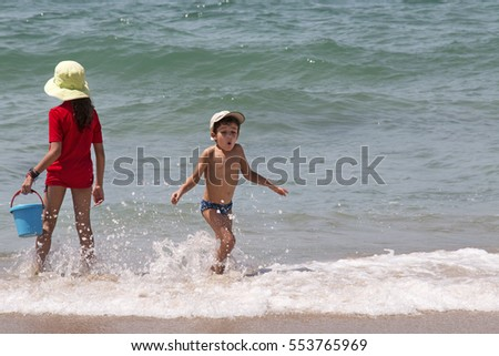 Back view of a girl and a boy playing at a beach in Brazil.