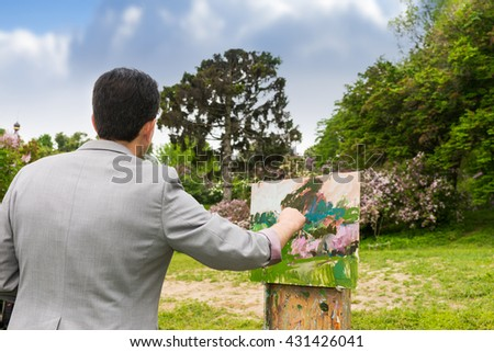 Back view of a handsome middle-aged male artist with his sketchbook in the park  working  on a trestle and easel painting with oils and acrylics during an art class - stock photo