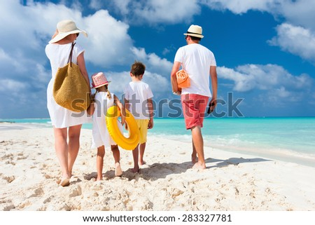 Back view of a happy family at tropical beach on summer vacation - stock photo