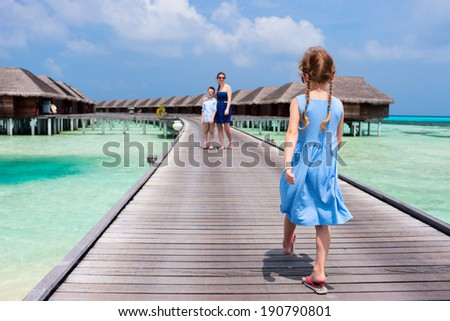 Back view of a little girl walking toward her family on wooden jetty at resort - stock photo