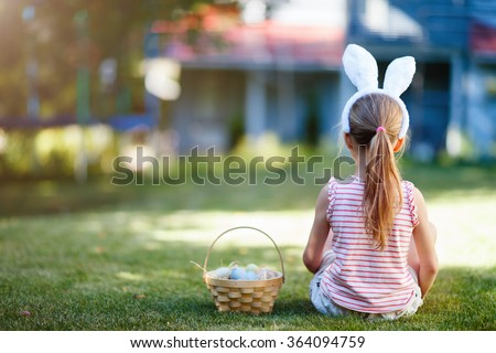 Back view of a  little girl wearing bunny ears with a basket of colorful Easter eggs outdoors on spring day
