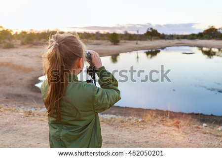 Back view of a little girl with binocular on safari near watering hole