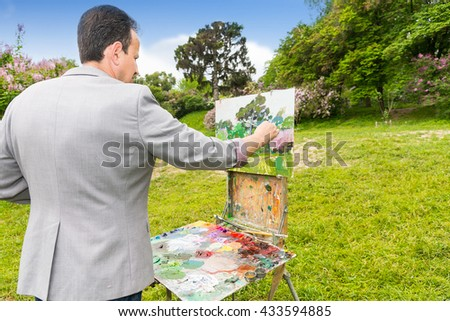 Back view of a male artist finishing his picture on a sketchbook standing in a garden in front of beautiful blue sky - stock photo