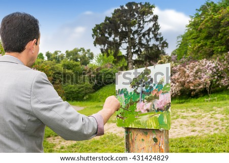 Back view of a male artist working outdoors in the park or garden on a trestle and easel painting with oils and acrylics during an art class - stock photo