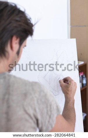 back view of a man drawing with a pencil on canvas at his painting studio - focus on the drawing - stock photo
