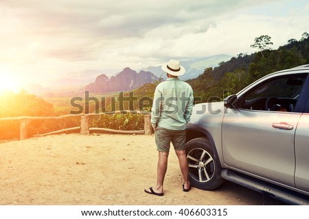 Back view of a man is thinking about this amazing world, while is standing on a mountain against jungle view. Young male traveler is enjoying beautiful landscape during road trip on suv in Thailand - stock photo