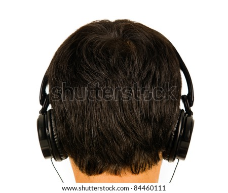 Back view of a man listening music with headphones. ( focus on head ) - stock photo