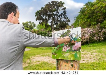 Back view of a man painter working outdoors in the park or garden on a trestle and easel painting with oils and acrylics during an art class - stock photo